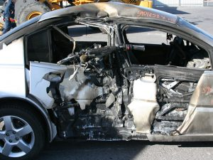 Motorcycle and vehicle that sustained severe fire damage caused by a fuel tank failure.
